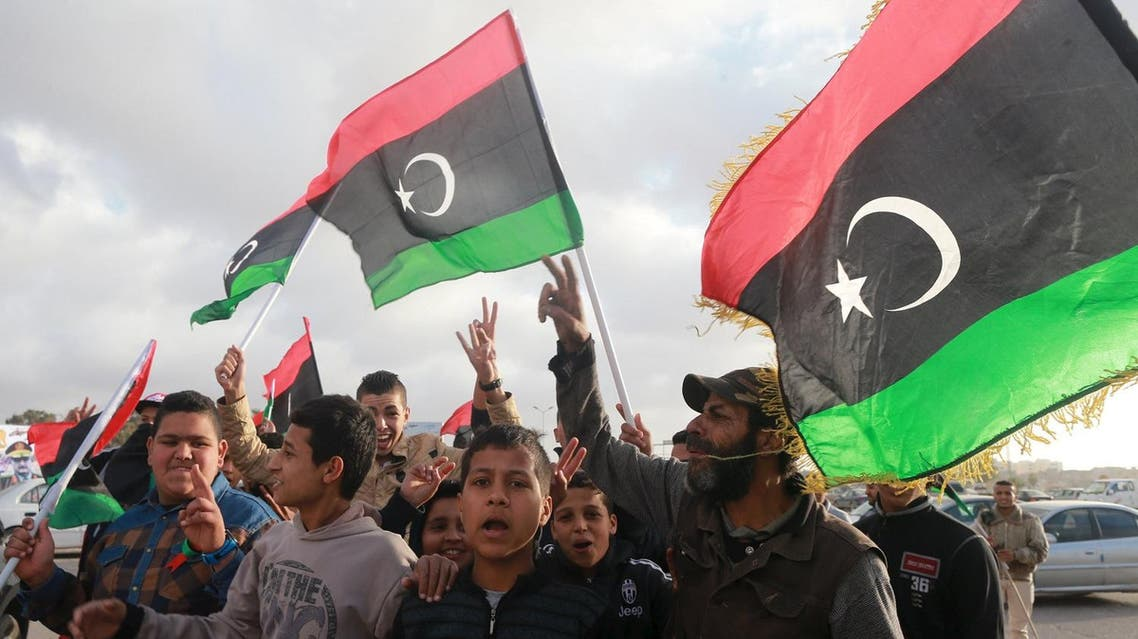 Libyans wave their national flags as they celebrate Libya's eastern government's gains in the area, in Benghazi, Libya, February 24, 2016. REUTERS