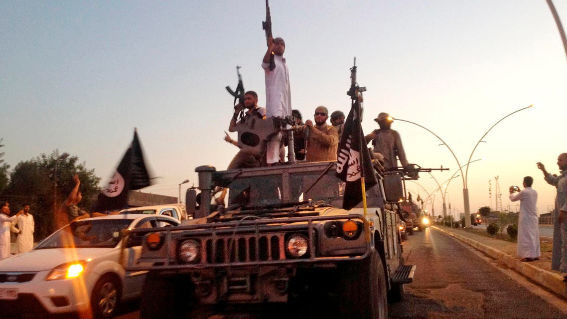 In this photo taken Monday, June 23, 2014, fighters from the Islamic State group parade in a commandeered Iraqi security forces armored vehicle down a main road at the northern city of Mosul, Iraq. AP