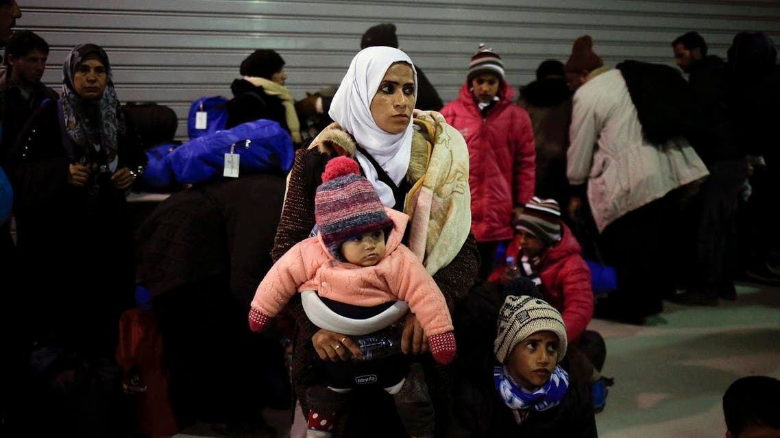 A woman holds her two children inside a terminal, following the arrival of refugees and migrants aboard the passenger ferry Blue Star Patmos at the port of Piraeus, near Athens, Greece, February 22, 2016. REUTERS