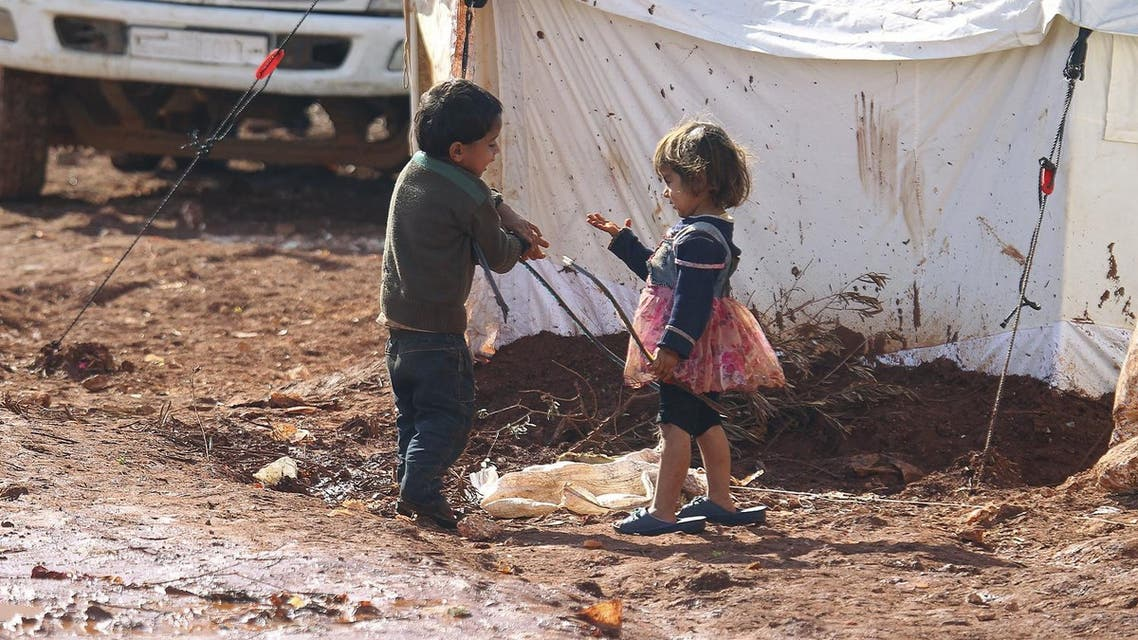 Children play outside tents housing internally displaced people in Atma camp, near the Syrian-Turkish border in Idlib Governorate. (Reuters)