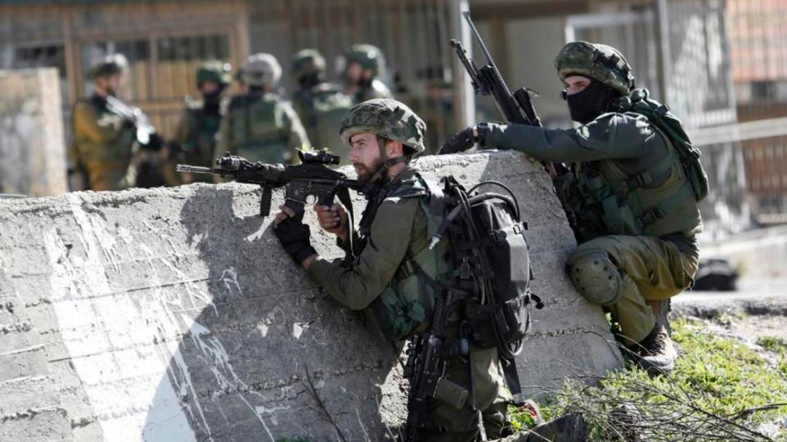 In this Monday, Feb. 15, 2016 file photo, Israeli soldiers take positions during a raid to arrest a Palestinian at the Amari Palestinian refugee camp, near the West Bank city of Ramallah during clashes with Palestinians that erupted after they entered the camp early in the morning. Palestinian officials say Israeli military raids in Palestinian-controlled territory have dramatically increased since a wave of violence erupted five months ago _ undermining the public's trust in their own security forces and jeopardizing one of the last areas of official contact between Israel and the Palestinians (AP)