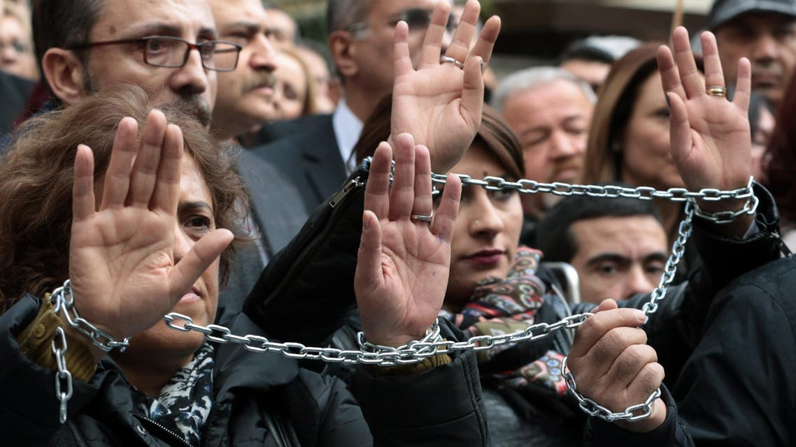 Journalists with chained hands protest against the jailing of opposition Cumhuriyet newspaper's editor-in-chief Can Dundar and Ankara representative Erdem Gul, in Ankara, Turkey, Friday, Nov. 27, 2015.  (AP)