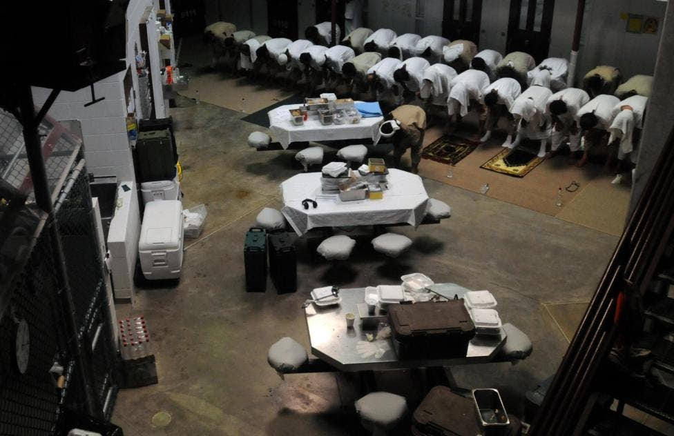 Detainees pray in a communal area of Camp Six, March 18, 2011. (Reuters)