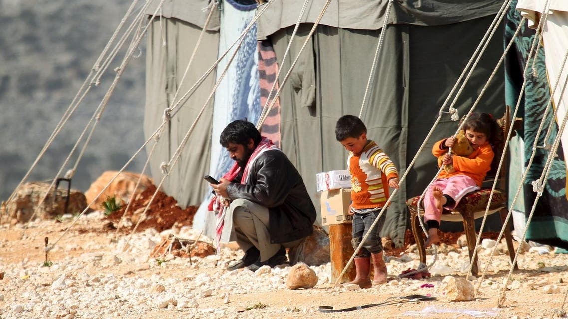 An internally displaced Syrian family that fled from Aleppo rests near tents in the village of Batabo, northern Idlib countryside, Syria, February 14, 2016. REUTERS