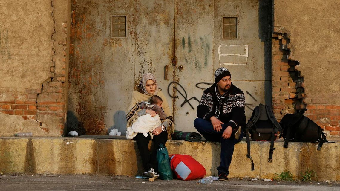 A family sits after the arrival of refugees and migrants from the eastern Greek islands to the Athens' port of Piraeus, Friday, Feb. 26, 2016. AP