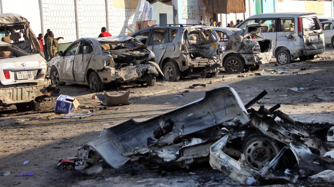 Somalis walk past the wreckage of vehicles outside a beachfront restaurant, the site of a previous attack, Somalia, Friday, Jan. 22, 2016. (AP)