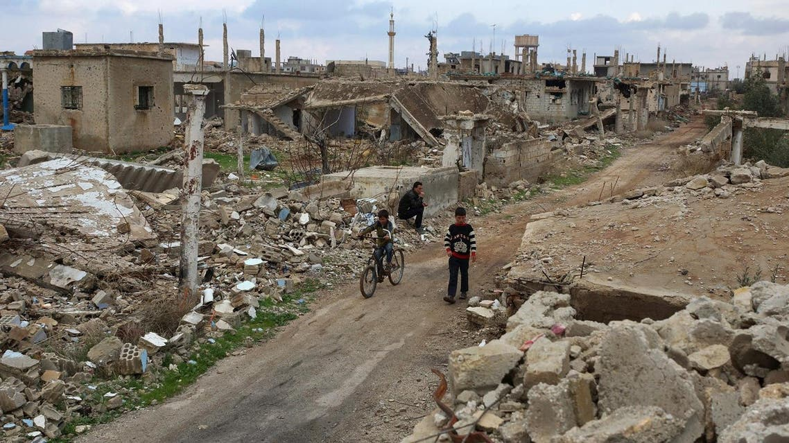 A boy rides a bicycle past a man sitting on rubble of a damaged house in the rebel held historic southern town of Bosra al-Sham, Deraa. (Reuters)