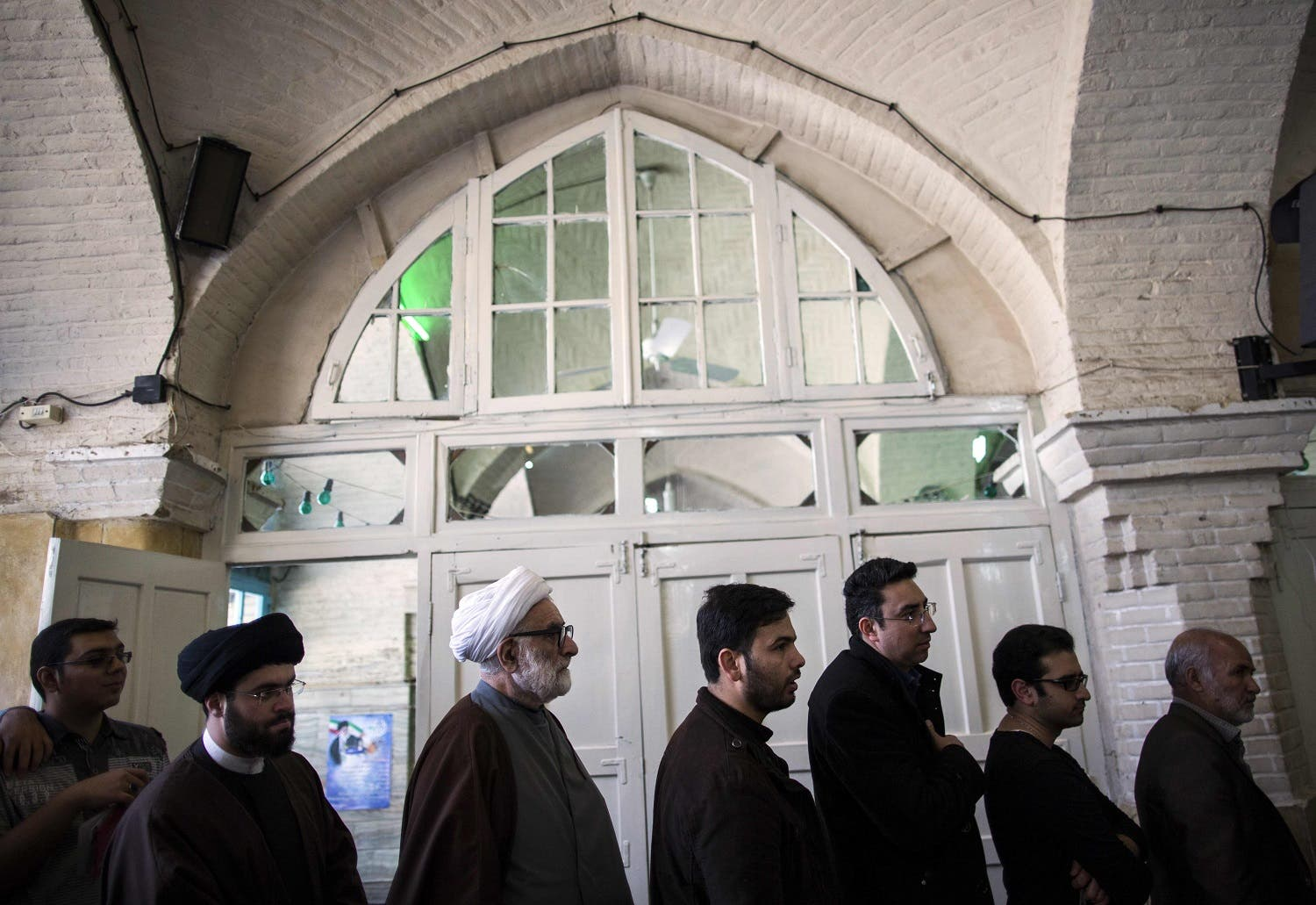 Iranians line up to vote for both parliamentary elections and the Assembly of Experts at a polling station in the holy city of Qom, 130 kms south of Tehran. (AFP)