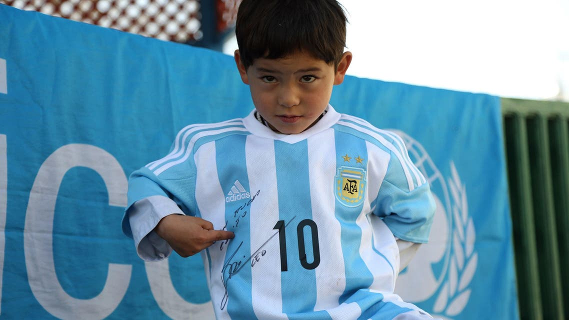 This handout photograph taken and released on February 25, 2016 by UNICEF Afghanistan shows five-year-old Afghan boy Murtaza Ahmadi posing with a jersey sent to him by Argentine football star Lionel Messi. (AFP)
