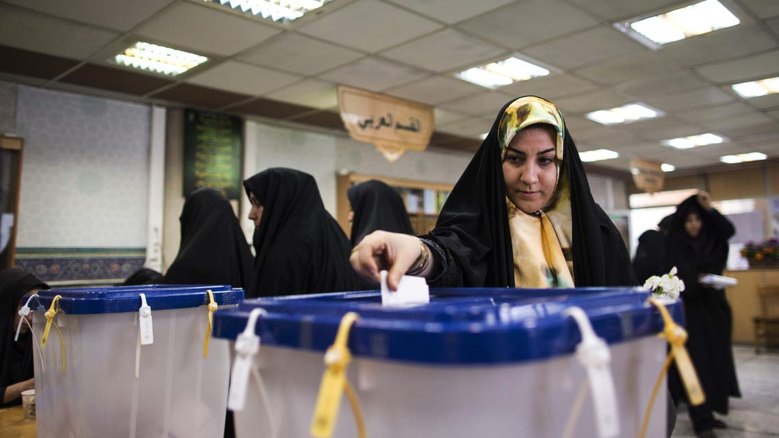 An Iranian woman casts her ballot to vote for both parliamentary elections and Assembly of Experts at a polling station at Massoumeh shrine in the holy city of Qom, 130 kms south of Tehran, on February 26, 2016. AFP