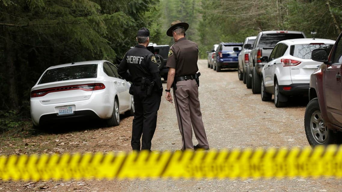 Mason County Sheriff's Chief Criminal Deputies Russ Osterhout, left, and Ryan Spurling, right, stand on a road near the scene of a fatal shooting Friday, Feb. 26, 2016, near Belfair, Wash. AP