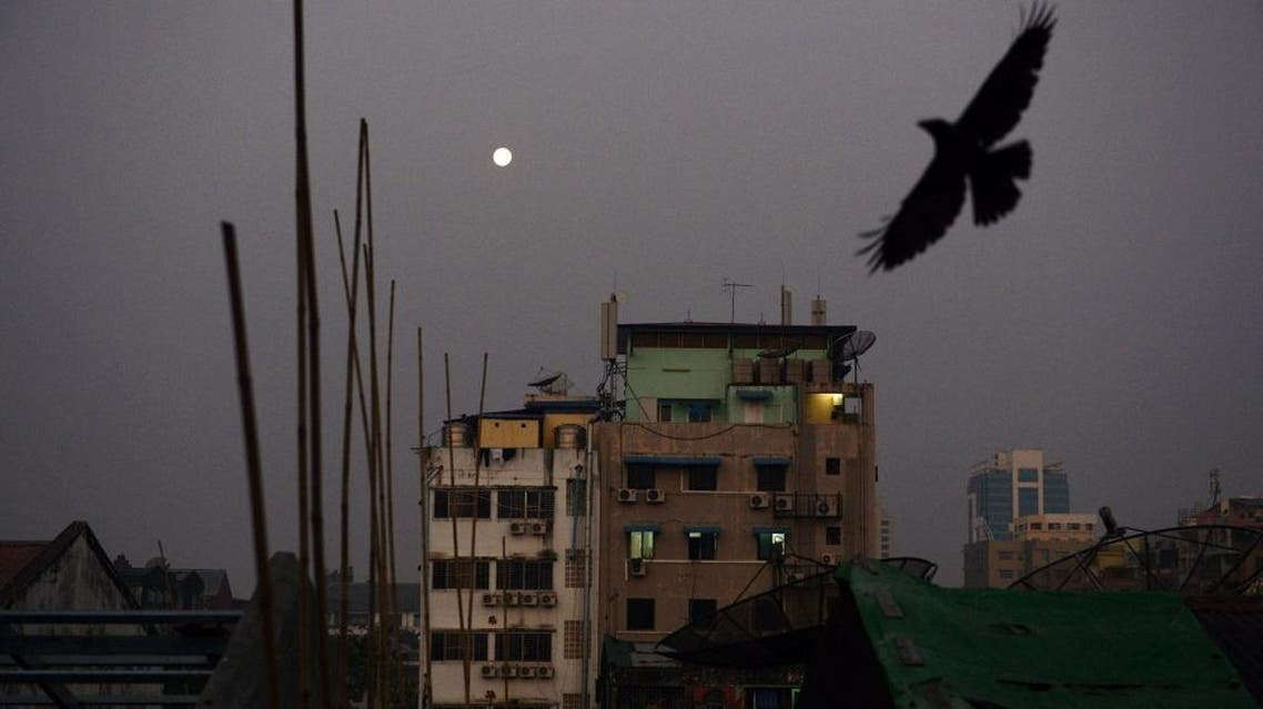 A crow flies over rows of residential apartments as the full moon descends at dawn over Yangon on February 24, 2016. AFP PHOTO / ROMEO GACAD