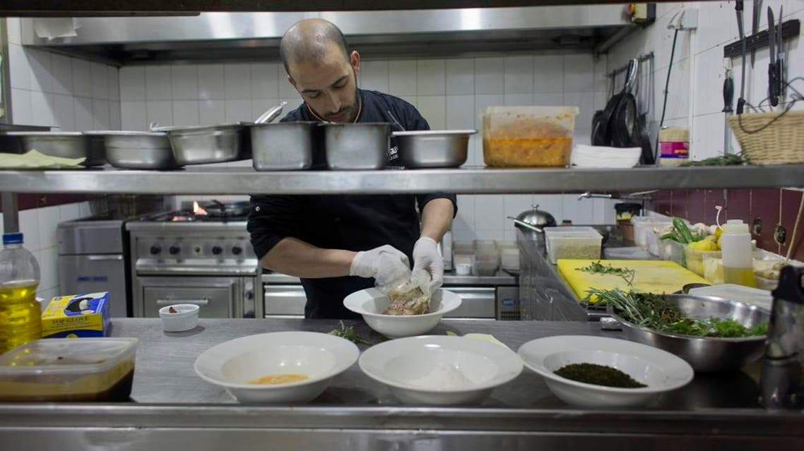 In this photo taken on Saturday Feb. 20, 2016, Palestinian chef Jihad al-Maharmeh prepares a mixed Palestinian French dish, Freekeh lamb rack at Orjuwan restaurant in the West Bank city of Ramallah. At a time of simmering Mideast tensions and rising malaise, a group of French chefs recently visited the West Bank to bring a little joie de vivre to Palestinian kitchens.(AP Photo/Nasser Nasser)