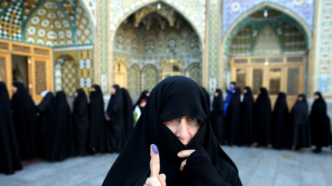 An Iranian woman displays her ink-stained finger after voting in the parliamentary and Experts Assembly elections at a polling station in Qom, 125 kilometers south of the capital Tehran, Iran, Friday, Feb. 26, 2016. (AP)