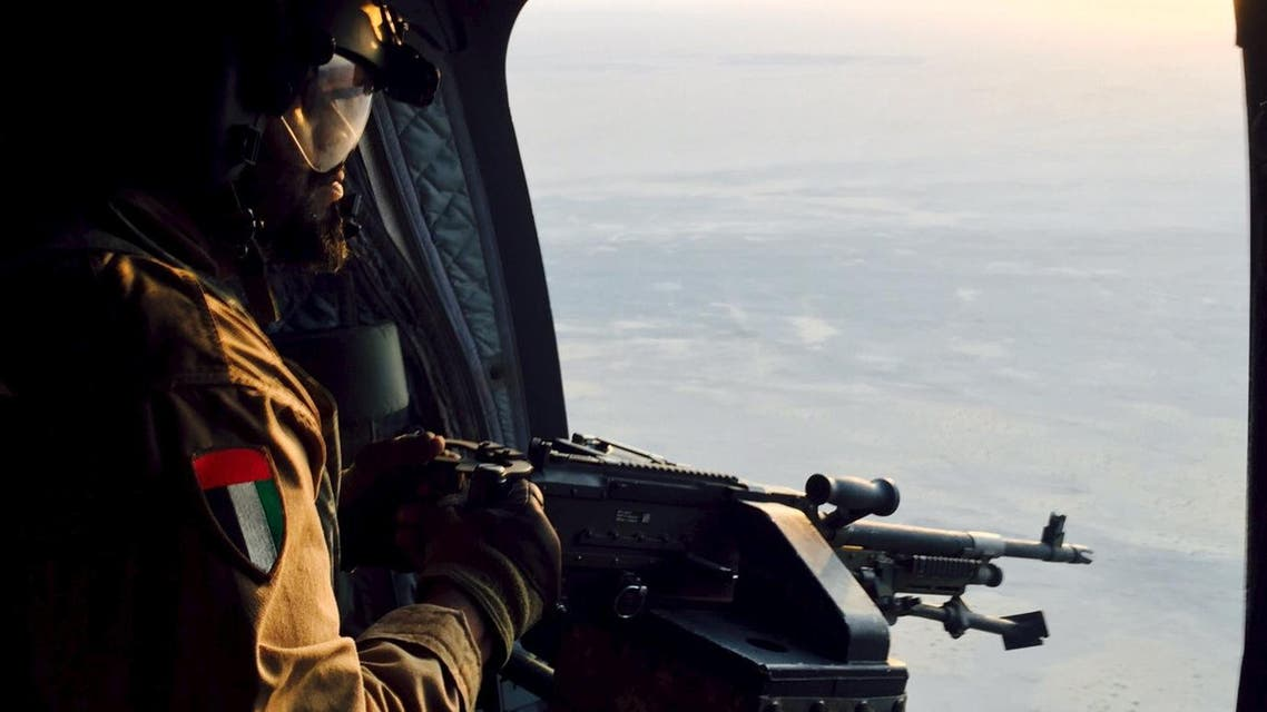 A soldier from the United Arab Emirates armed with a machine gun watches over Yemeni territory while riding a Chinook helicopter en route to a Saudi-led coalition air base in the kingdom September 17, 2015. (Reuters)