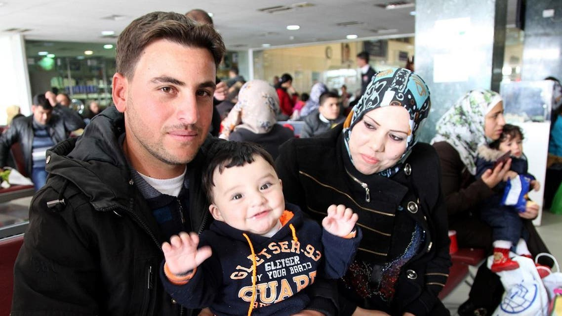 Radi poses for a photo with his son and wife, who names are omitted for security reasons, while waiting in an airport in Amman, Jordan, to board a plane to Canada where they will be resettled, Sunday, Dec. 20, 2015. (AP)