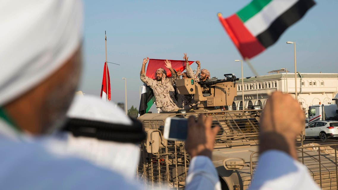 Emirati people wave the national flag as a convoy of UAE military vehicles and personnel travels from a UAE army base marking their retuurn from Yemen, United Arab Emirates, Saturday, Nov. 7, 2015. (AP)