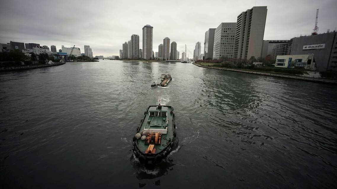 In this Nov. 26, 2015 photo, a tugboat pulls floating scaffold on Sumida River next to a super dyke, right, in Tokyo. AP