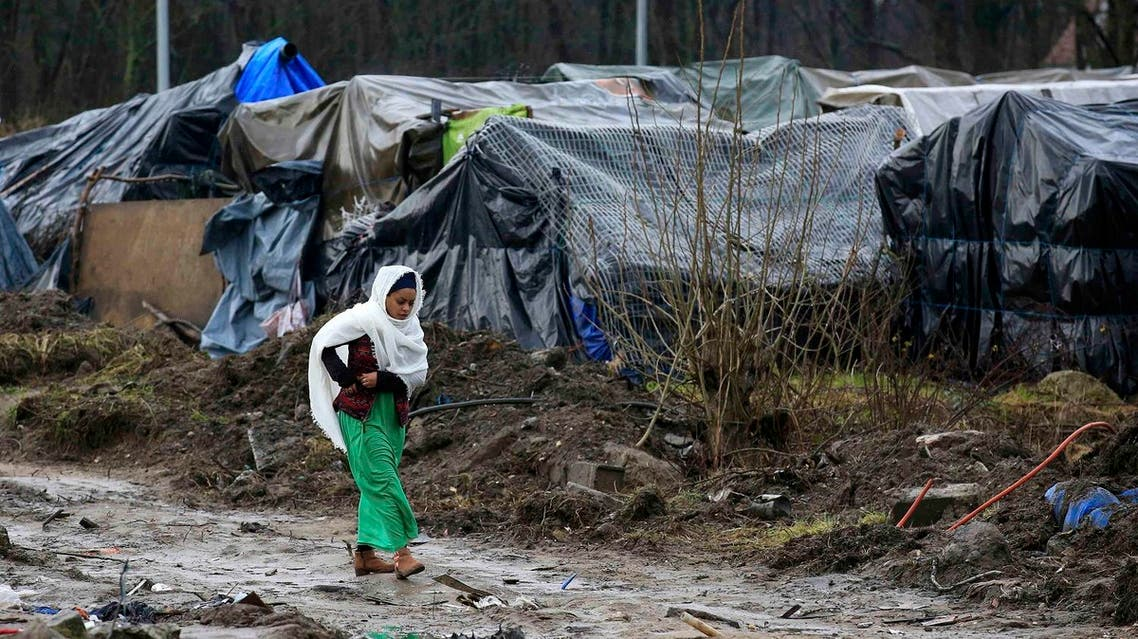"""An Eritrean migrant walks in the mud in the southern part of a camp for migrants called the """"jungle"""", in Calais, northern France, February 24, 2016. Reuters"""