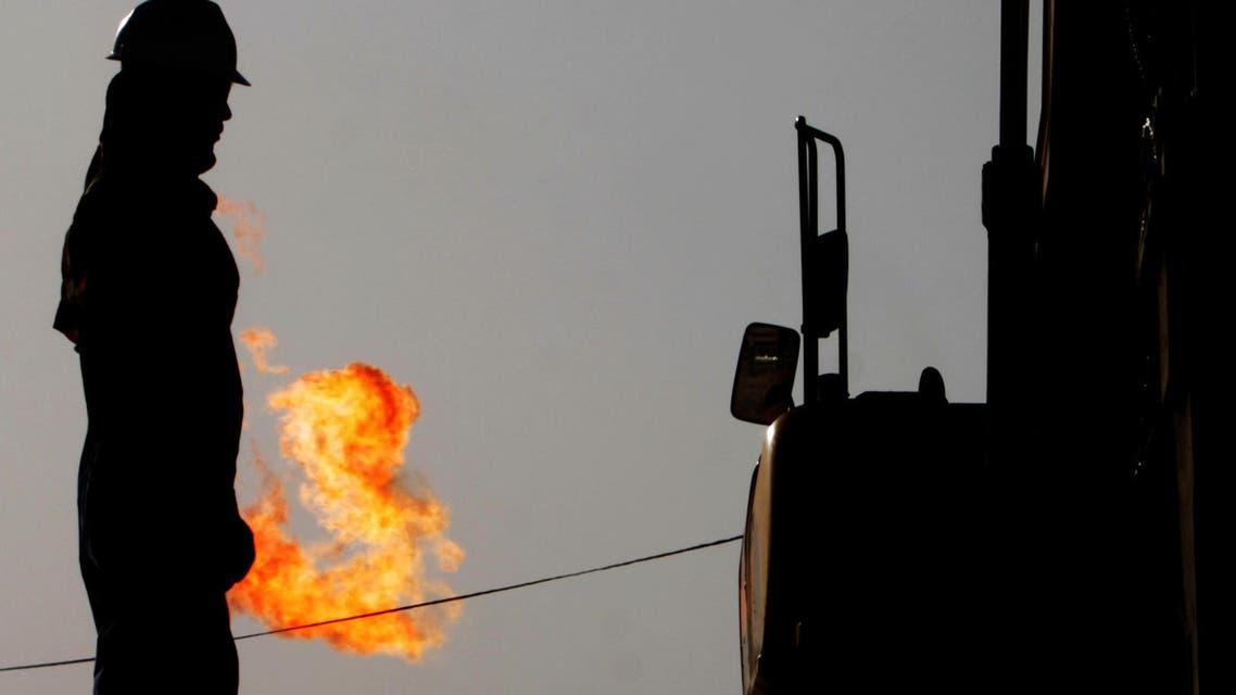 A gas flame burns behind oil field workers in the desert oil fields of Sakhir, Bahrain. (AP)