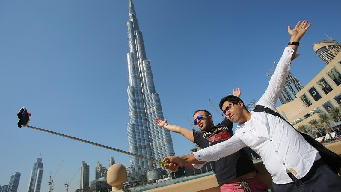 "In this Tuesday, Jan. 6, 2015 photo, Rasul Alekberov holds a selfie stick next to his friend Gudrat Aghayev both tourists from Republic of Azerbaijan while they take a selfie in front of ""Burj Khalifa"". (AP)"