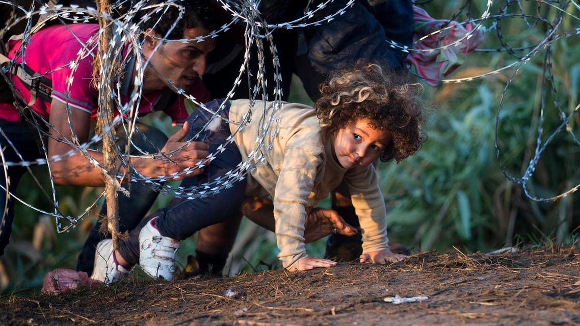 A child is helped cross from Serbia to Hungary through the barbed wire fence near Roszke, southern Hungary. (File photo: AP)