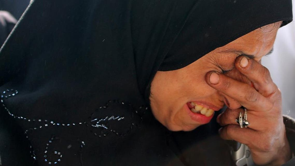 In this Feb. 24, 2014 file photo released by the United Nations Relief and Works Agency for Palestine Refugees in the Near East (UNRWA), a resident of the besieged Palestinian camp of Yarmouk weeps as she waits to receive humanitarian aid from UNRWA in Damascus, Syria. Over the past two years, the ability of humanitarian groups to deliver aid to Syrians has become increasingly difficult. (UNRWA via AP, File)