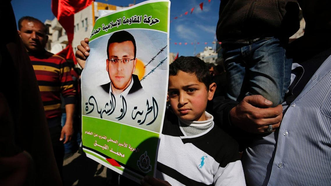 Palestinians hold placards depicting a portrait of journalist Mohammed al-Qiq imprisoned by Israel, as they celebrate the announcement to end his 94-day hunger strike under a deal for his release in May. (AFP)