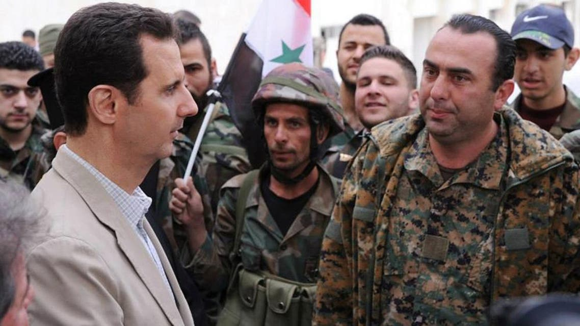 In this file photo taken on Sunday April 20, 2014 and released by the Syrian official news agency SANA, Syrian President Bashar Assad, left, talks to government soldiers during his visit to the Christian village of Maaloula, near Damascus, Syria. (SANA via AP, File)
