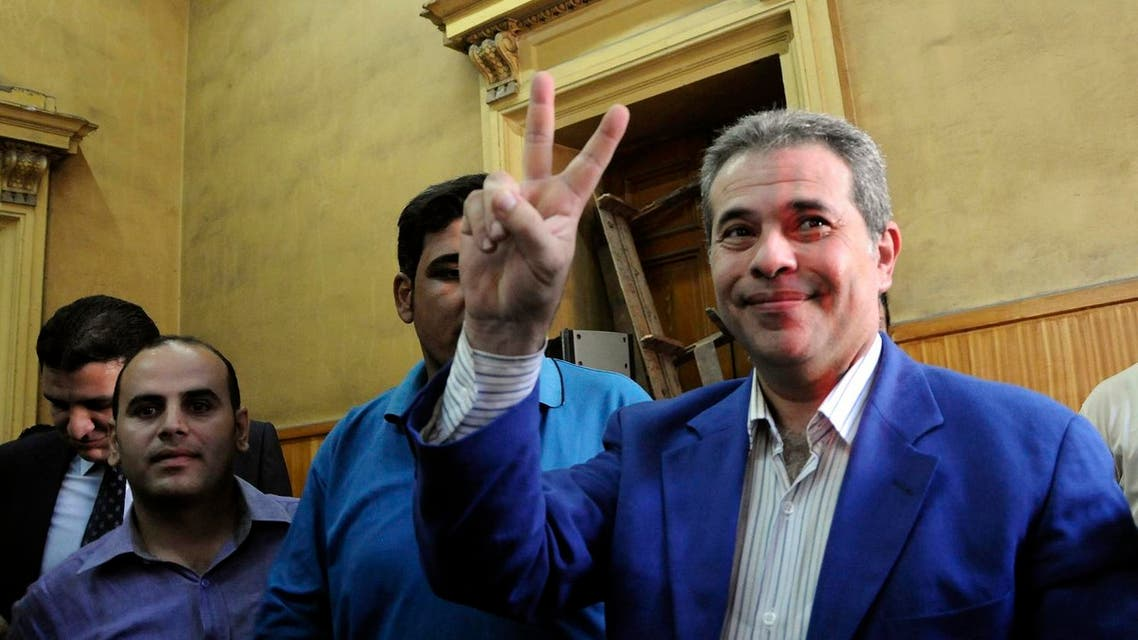 In this Saturday, Sept. 1, 2012 file photo, Tawfiq Okasha, center, a popular Egyptian TV presenter accused of inciting the killing of the country's new president on air, flashes the victory sign as he arrives for the opening of his trial, in Cairo, Egypt. Okasha has been expelled from parliament over a meeting he had with the Israeli ambassador to Egypt, which in 1979 became the first Arab nation to sign a peace treaty with Israel. (AP Photo/Mohammed Assad, File)