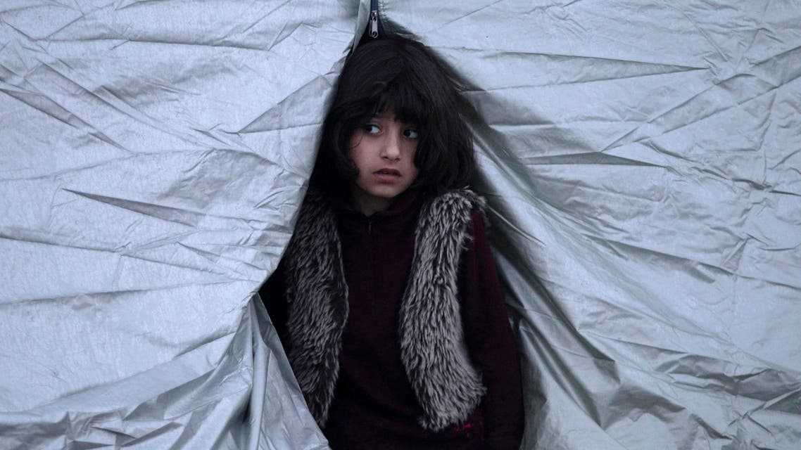 A girl looks out from a tent at a relocation camp where stranded refugees and migrants wait to cross the Greek-Macedonian border, near the Greek village of Idomeni, March 1, 2016. (Reuters)