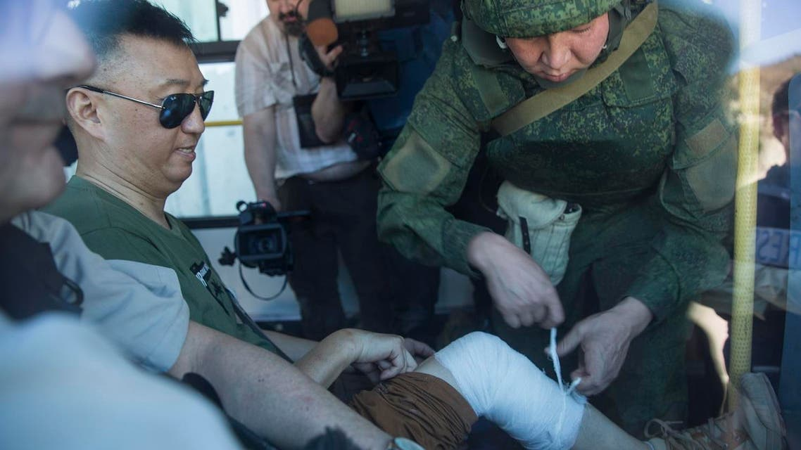 A Chinese reporter is bandaged by Russian military officer after he fell while moving to safety during explosions in Kinsibba, Syria, near the border with Turkey. (AP)