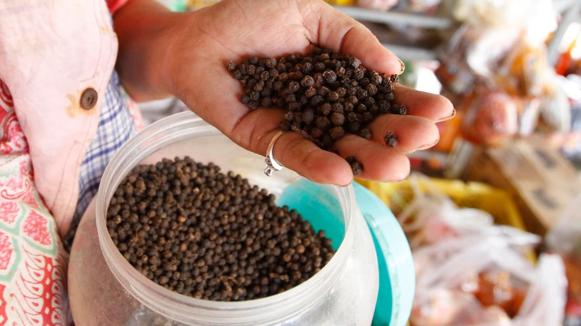 In this Tuesday, March 1, 2016 photo, a vendor holds a handful of Kampot pepper before selling at a market in Phnom Penh, Cambodia, Tuesday, March 1, 2016. Cambodia's Kampot pepper has joined an elite group of gourmet food items whose names are protected by the European Union. The EU said Tuesday that Kampot pepper was officially registered as having Protected Geographical Indication status, or PGI, on Feb. 18, making it the first Cambodian product to receive the label. (AP Photo/Heng Sinith)