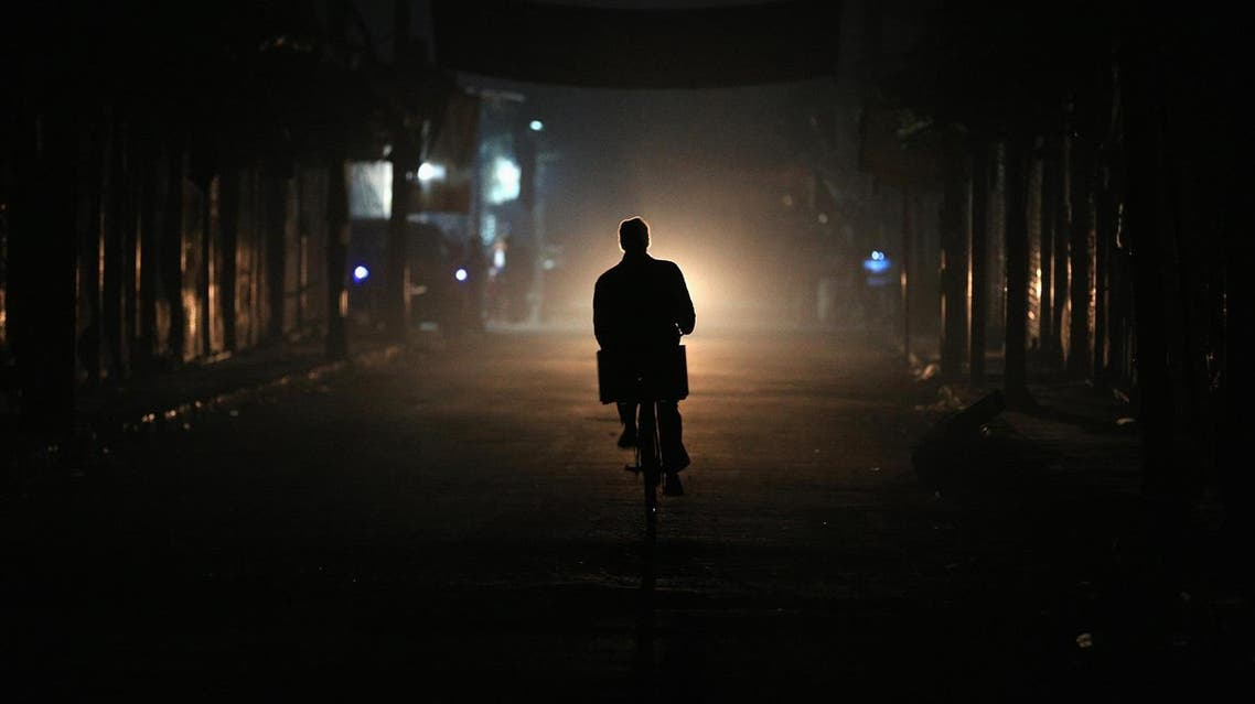 A resident drives a motorbike at night on New Year's Eve in eastern al-Ghouta. (Reuters)