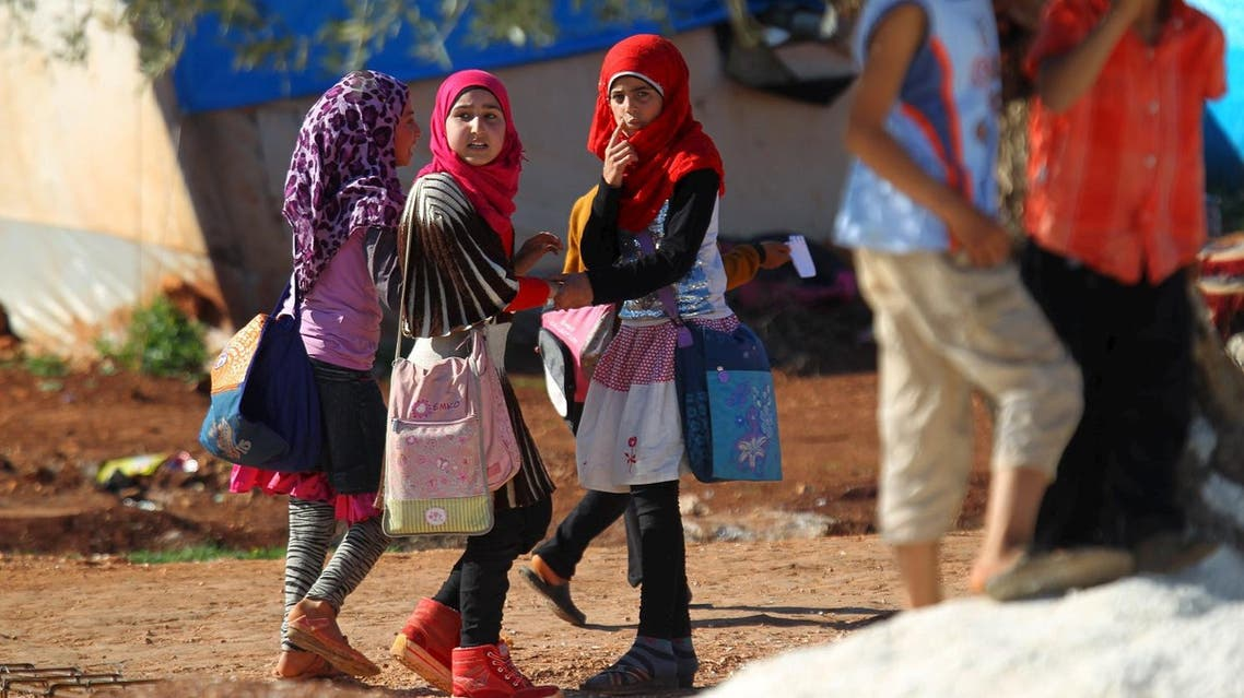 Internally displaced Syrian girls carry school bags inside Safsafa camp, northern Idlib countryside. (Reuters)