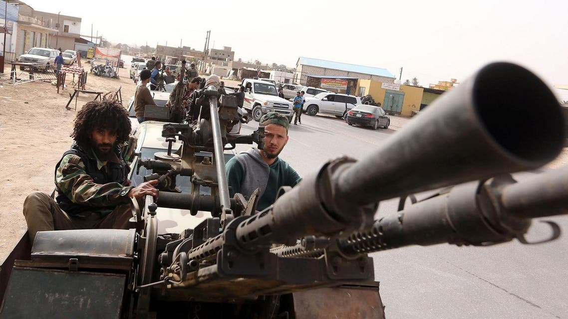 Members of a brigade loyal to the Fajr Libya (Libya Dawn), an alliance of Islamist-backed fighters, drive pick up trucks mounted with machine guns during a military parade following battles against ISIS. (AFP)