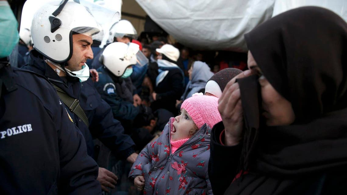 Migrants who are waiting to cross the Greek-Macedonian border, stand in front of police officers in a makeshift camp, near the Greek village of Idomeni March 2, 2016. (Reuters)
