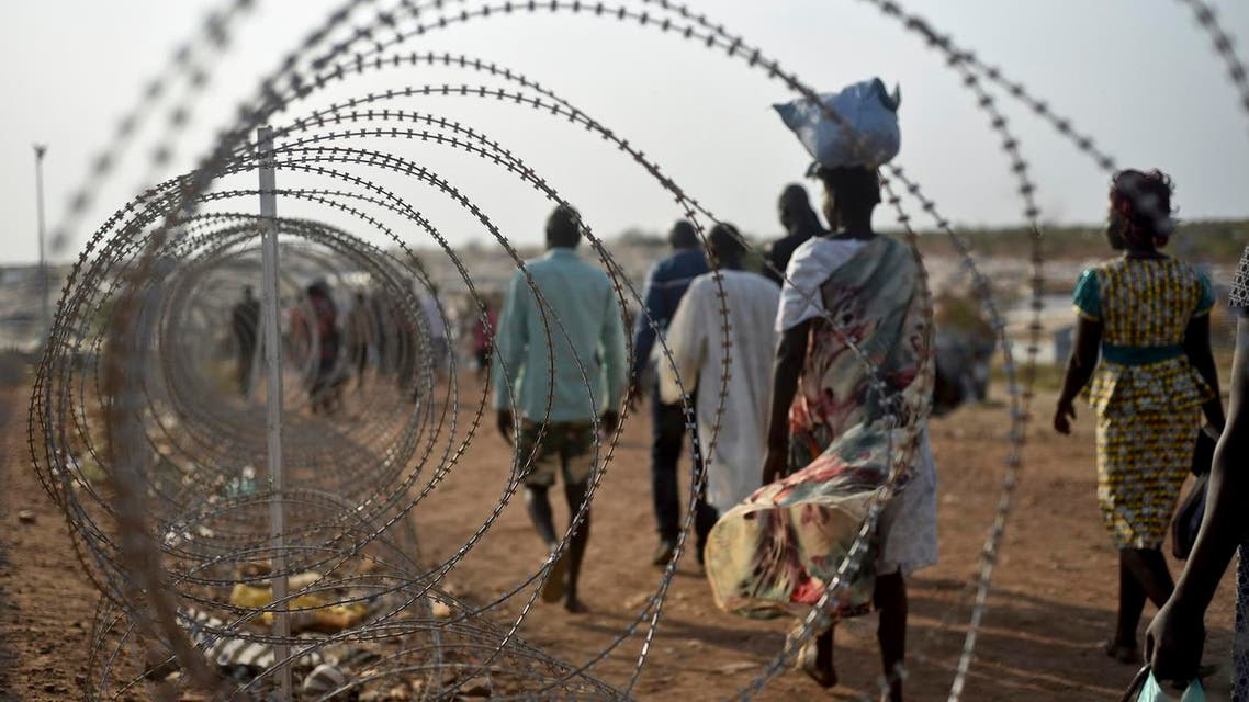 In this photo taken Tuesday, Jan. 19, 2016,displaced people walk next to a razor wire fence at the United Nations base in the capital Juba, South Sudan. AP