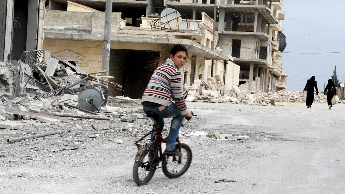 A boy rides a bicycle near damage in Kafr Hamra village, northern Aleppo countryside, Syria February 27, 2016. Picture taken February 27, 2016. REUTERS/Abdalrhman Ismail