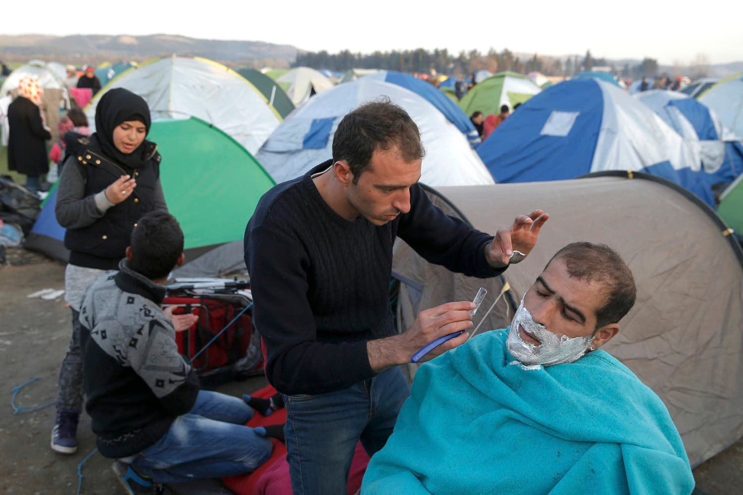 A migrant shaves the face of another in a makeshift camp, near the Greek village of Idomeni March 2, 2016. Reuters