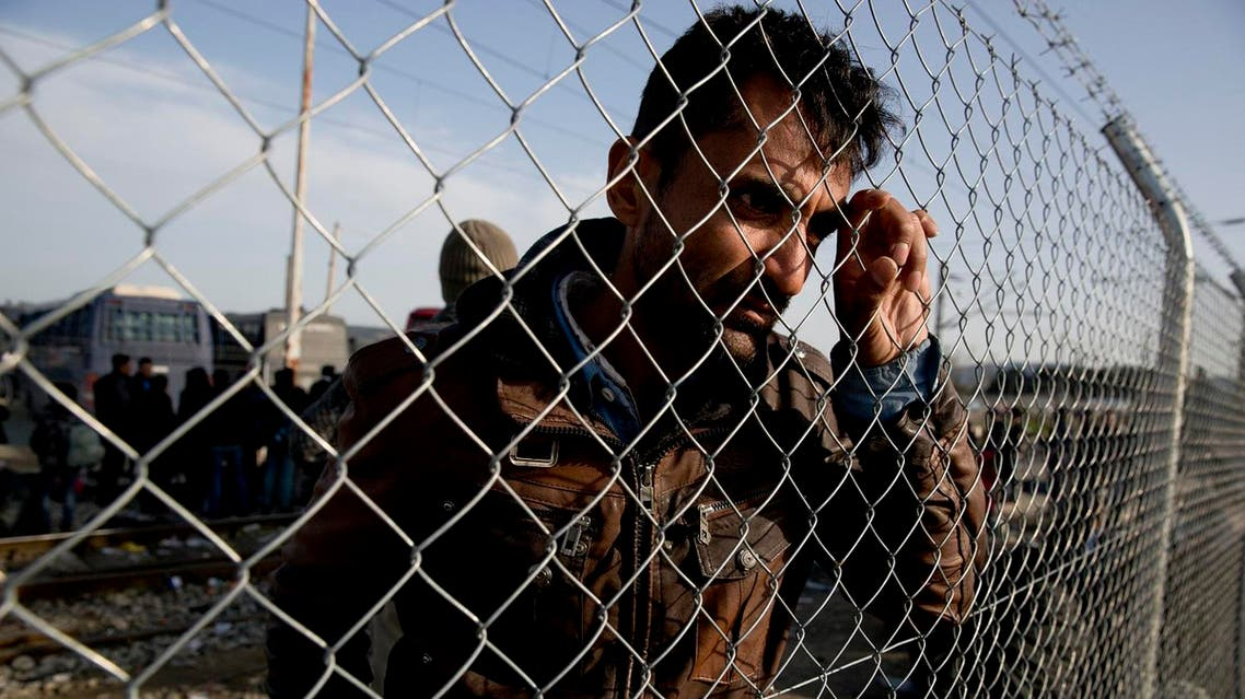 An Afghan migrant waits behind a fence to board a bus in the northern Greek border station of Idomeni. (File photo: AP)