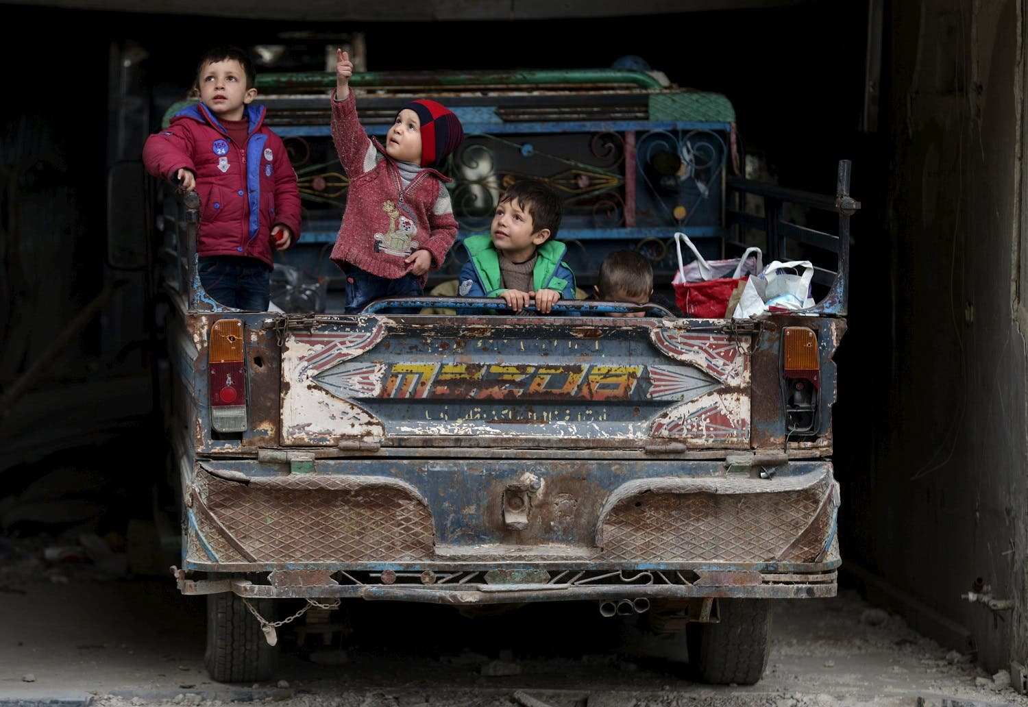 A boy gestures as he sits with others on a pick-up truck in the rebel held Douma neighborhood of Damascus. (Reuters)