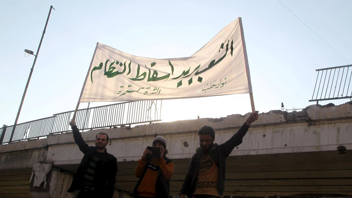 People carry a banner while attending a protest against forces loyal to Syria's President Bashar al-Assad, Russia and the Syrian Democratic forces, in Tariq al-Bab neighbourhood of Aleppo, Syria February 29, 2016. REUTERS