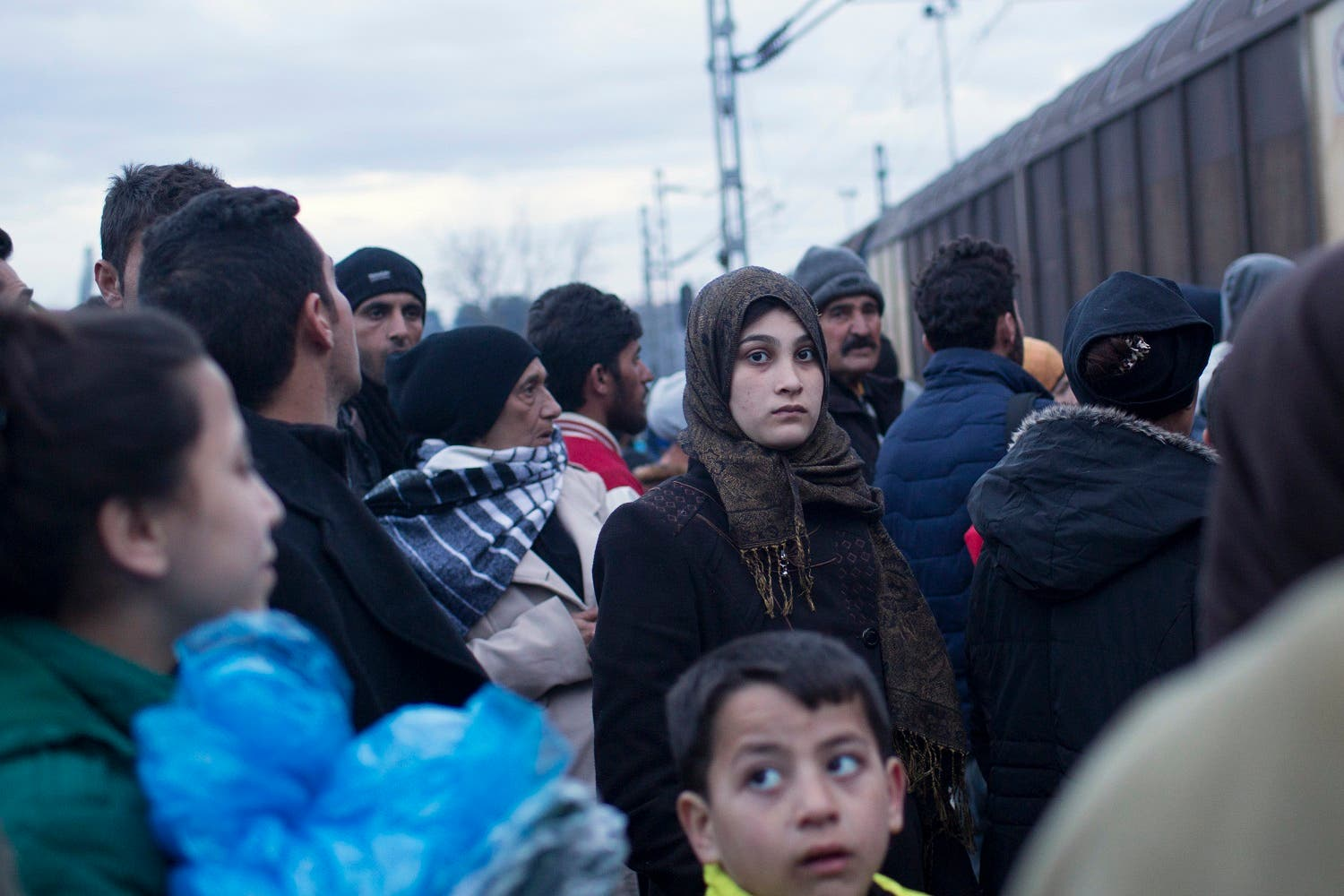 A woman stands in a crowd beside the railway tracks as a train passes beside a refugee camp where thousands of refugees are waiting to be allowed to cross the border into Macedonia in the northern Greek border station of Idomeni, Thursday, March 3, 2016. AP
