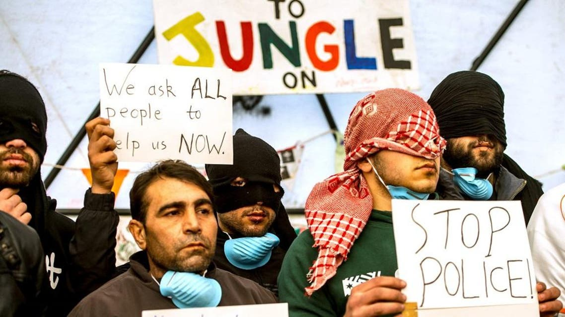 "Iranian migrants with their lips sewn shut hold signs at the ""Jungle"" migrant camp in the French port city of Calais on March 4, 2016 (AFP)"