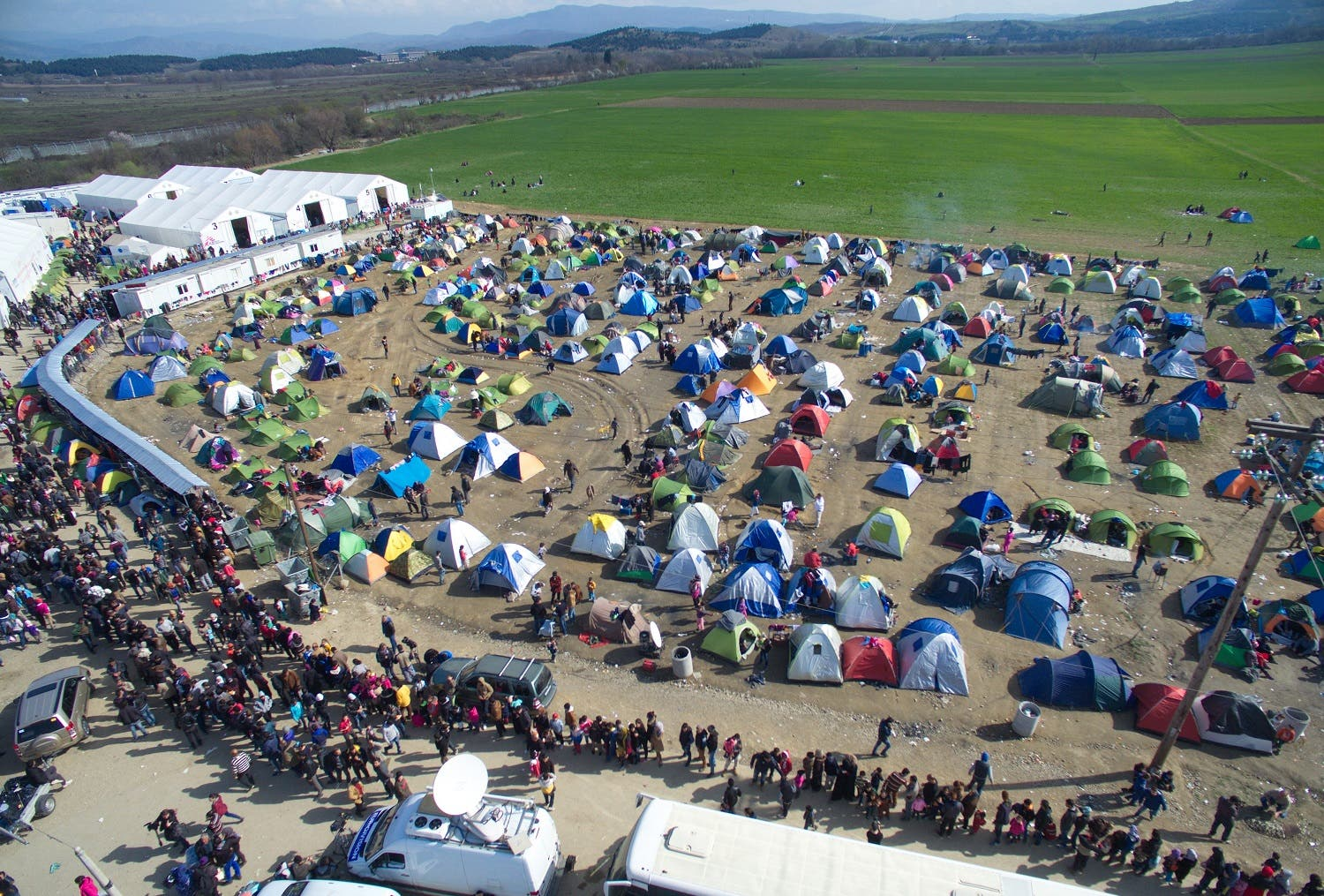 Refugees and migrants wait in queue to receive food distributed by non-governmental organization at a refugee camp at the Greek-Macedonian border, near the northern Greek village of Idomeni, Thursday, March 3, 2016. (AP)