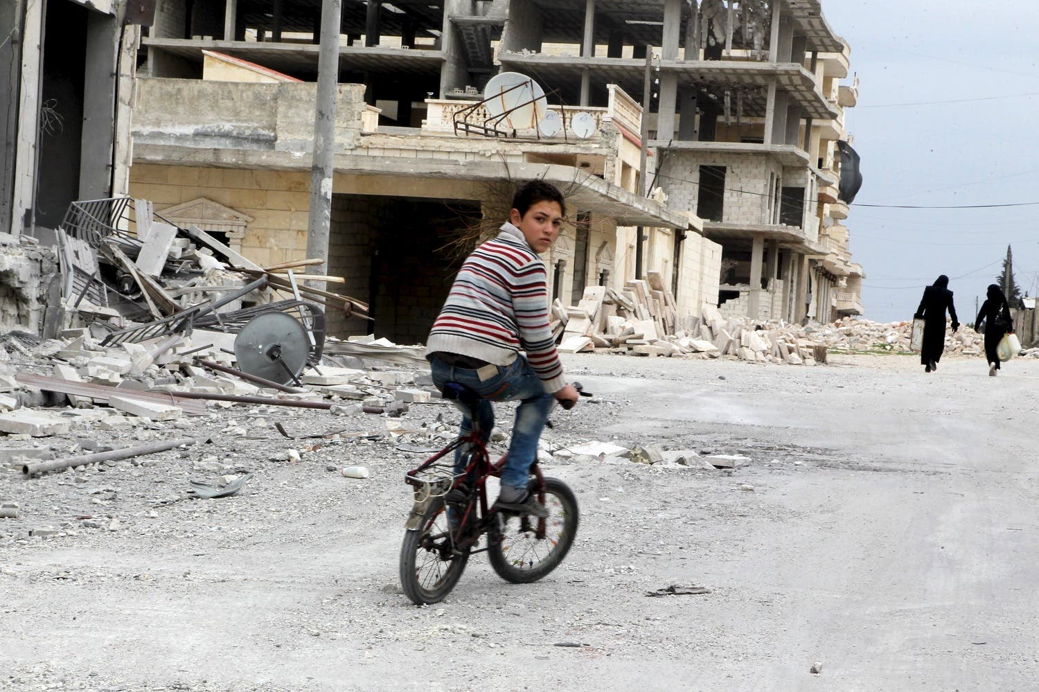A boy rides a bicycle near damage in Kafr Hamra village, northern Aleppo countryside. (Reuters)