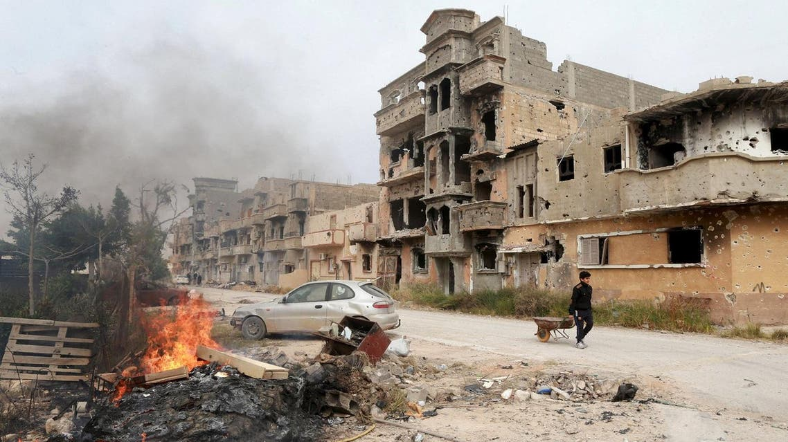 A man pulls a wheelbarrow past destroyed buildings after clashes between military forces loyal to Libya's eastern government and Islamist fighters, in Benghazi, Libya, February 28, 2016. REUTERS
