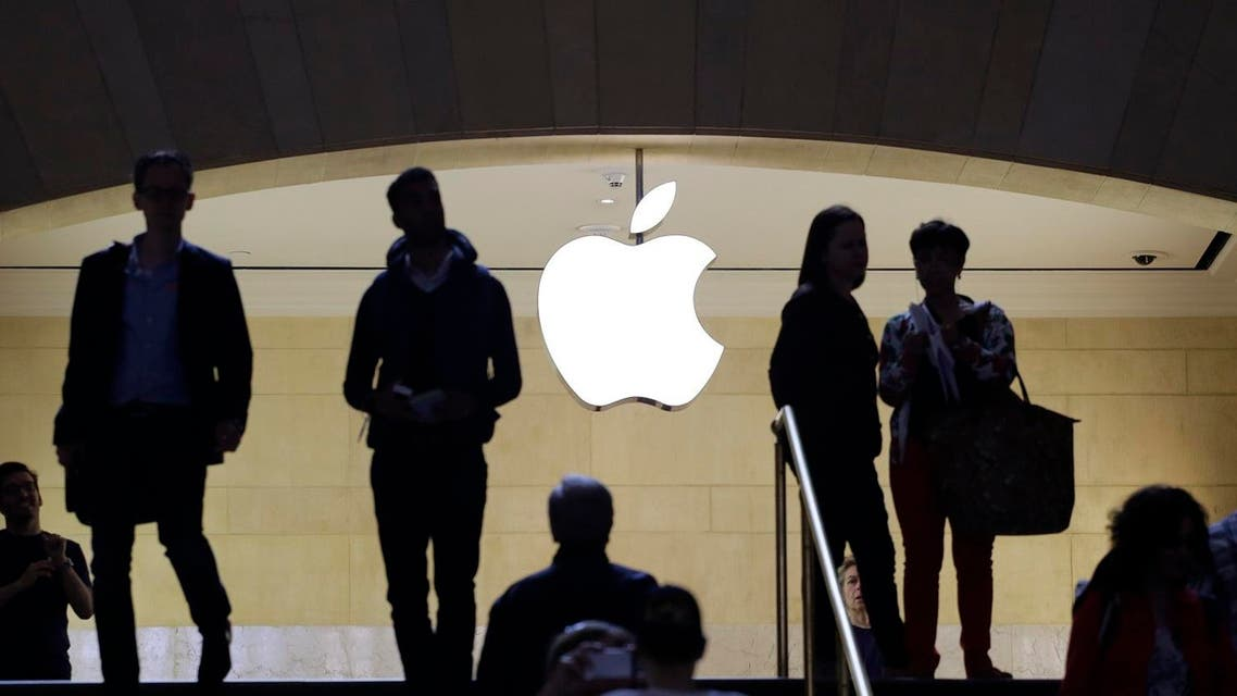 In this May 22, 2015 photo, customers and staff stand in the entrance to an Apple store in New York's Grand Central Terminal. AP