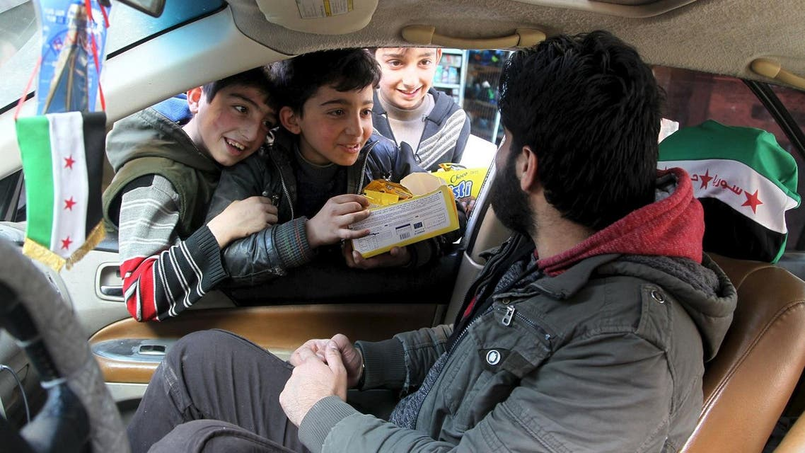 Boys try to sell biscuits to a man driving a car in Aleppo. (Reuters)
